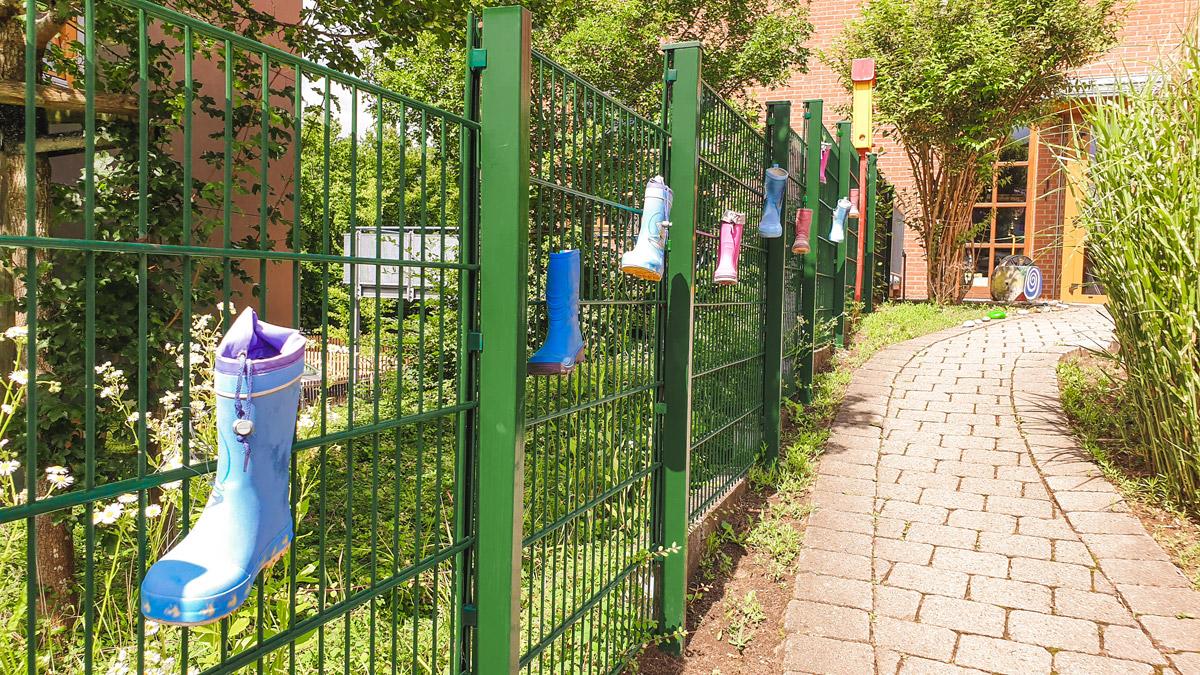 Gummistiefel an Zaun gebunden